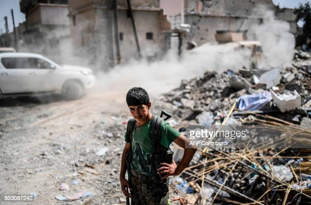 TOPSHOT A member of the Syrian Democratic Forces stands on a damaged street on the eastern frontline of Raqa on September 24 2017 Syrian fighters...