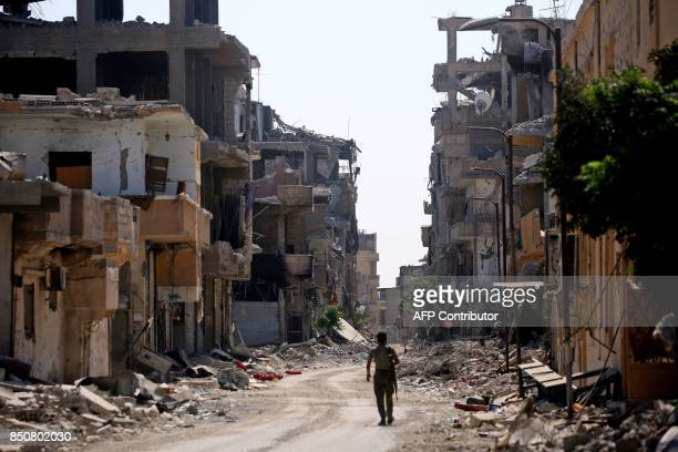 A member of the Syrian Democratic Forces swalks along a destroyed street in the former Islamic State stronghold of Raqa on September 21 2017 Syrian...