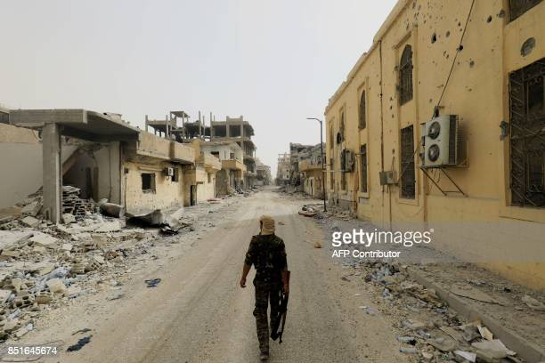 A member of the Syrian Democratic Forces walks in the former Islamic State stronghold of Raqa on September 22 as the Syrian fighters backed by US...