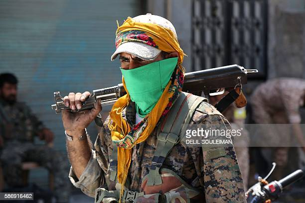 TOPSHOT A member of the Syrian Democratic Forces walks on a street with his weapon in the northern Syrian town of Manbij on August 7 as SDF comb the...