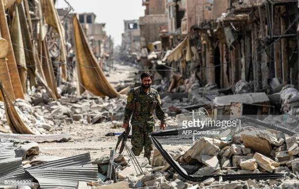 TOPSHOT A member of the Syrian Democratic Forces walks through the debris in the old city centre on the eastern frontline of Raqa on September 25...