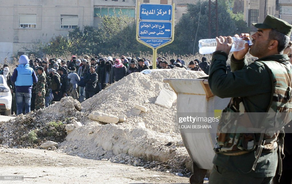 A member of the Syrian government forces drinks water as he stands guard while Syrian rebel forces begin evacuating the last oppositionheld district...