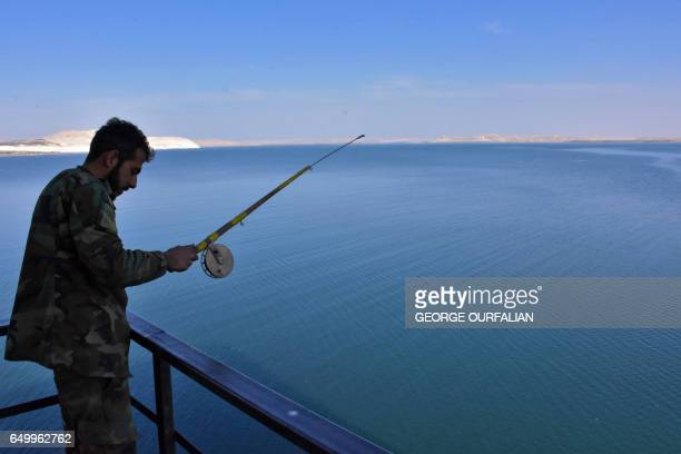 TOPSHOT A member of the Syrian government forces fishes at lake Assad near a water pumping station they retook the day before on the eastern...