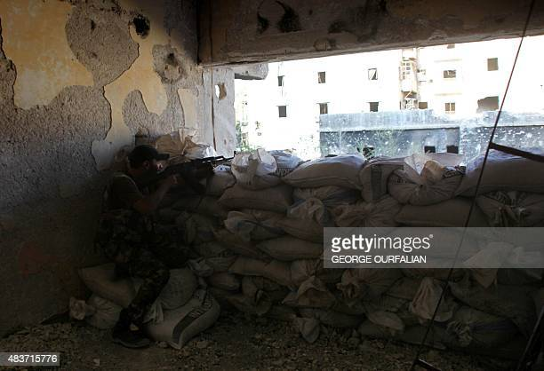 A member of the Syrian government forces guards a look out point in the Maysaloun neighbourhood of the northern embattled Syrian city of Aleppo on...