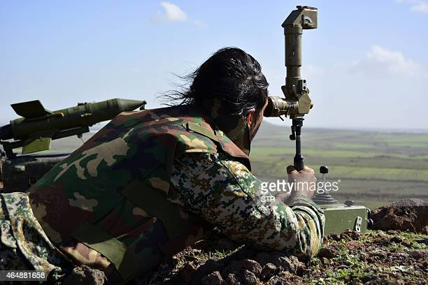 A member of the Syrian government forces looks at enemy positions from the Fatima hill overlooking the town of Kfar Shams north of the southern...