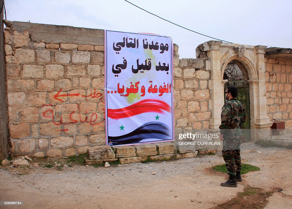 A member of the Syrian government forces looks at sign reading in Arabic: 'Our next upcoming conquest Fuaa and Kafraya' referring to the rebel-besieged towns in Syria's Idlib province after they took control of the village of Kiffin, on the northern outskirts of the embattled city of Aleppo on the road leading to Gaziantep, from opposition forces on February 11, 2016. / AFP / GEORGE OURFALIAN
