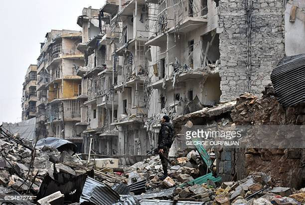 TOPSHOT A member of the Syrian government forces stands in a severely damaged street in Aleppo's newly captured AlKalasseh neighbourhood in the...