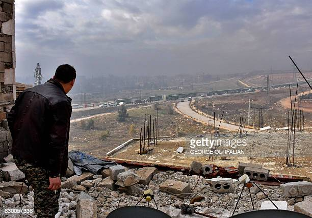 TOPSHOT A member of the Syrian government forces wacthes during an evacuation operation of Syrian rebel fighters and civilians from a oppositionheld...