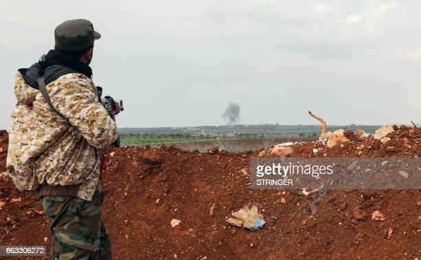 A member of the Syrian government forces watches smoke plumes rise from artillery fire near the town of Qumhanah in the countryside of the central...