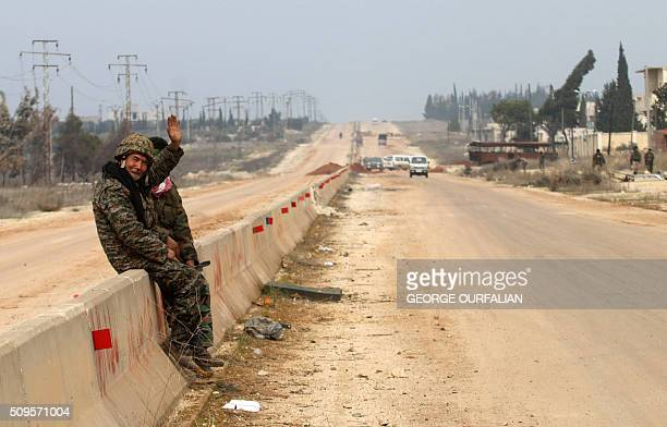 A member of the Syrian government forces waves as he sits on the road leading to Gaziantep on the outskirts of the village of Kiffin after they...