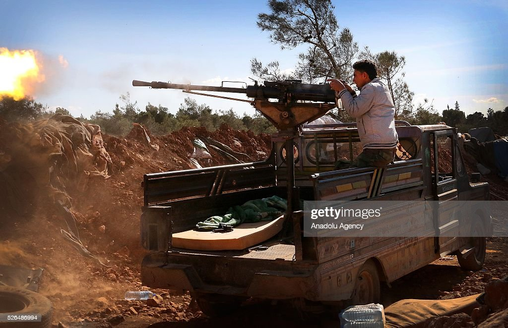 A member of the Syrian opposition forces fires a nachine gun during the clashes against the Shiite militia forces in Khan Tuman village in southern outskirts of Aleppo, Syria on April 29, 2016.