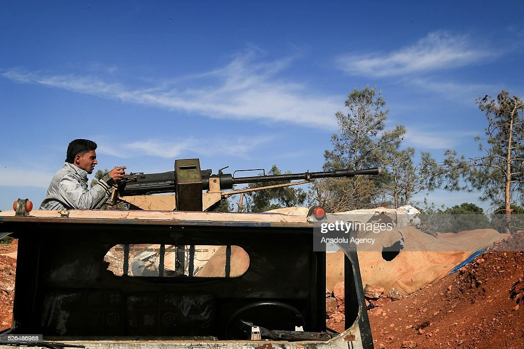 A member of the Syrian opposition forces uses a machine gun during the clashes against the Shiite militia forces in Khan Tuman village in southern outskirts of Aleppo, Syria on April 29, 2016.