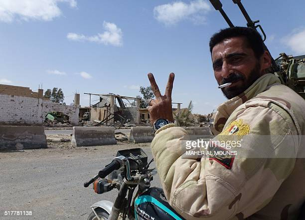 A member of the Syrian progovernment forces flashes the Vsign in a residential neighbourhood of the modern town of Palmyra on March 27 after troops...