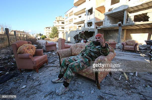 TOPSHOT A member of the Syrian progovernment forces sits on a sofa in the strategic town of Salma in the coastal Latakia province on January 15...