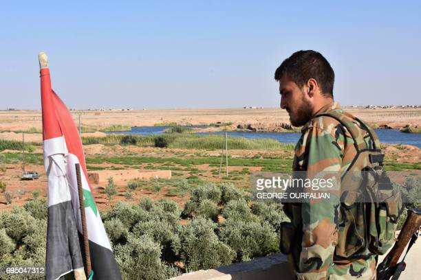 A member of the Syrian progovernment forces stands next to a Syrian flag looking out over Wadi Shatnat alMityhah an offshoot of Lake Assad in the...