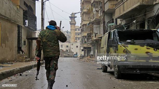 A member of the Syrian progovernment forces walks in eastern Aleppo's alKalasseh neighbourhood on December 13 2016 Civilians and opposition fighters...