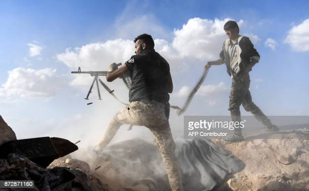 TOPSHOT A member of the Syrian proregime forces fires a machine gun as a comrade holds his feeding ammunition belt during the advance towards...