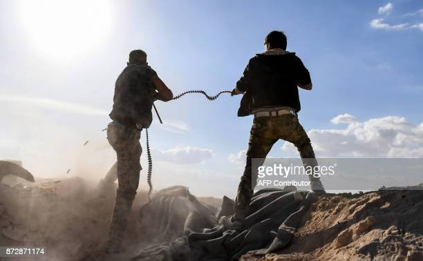 A member of the Syrian proregime forces fires a machine gun as a comrade holds his feeding ammunition belt during the advance towards rebelheld...