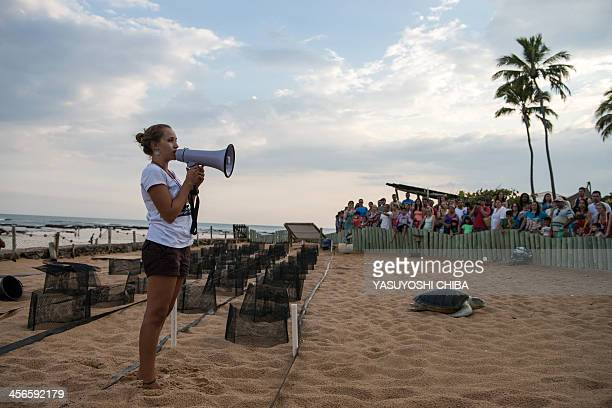 A member of the Tamar Project speaks to visitors at their headquarters in Praia do Forte Bahia state Brazil on December 13 2013 The Tamar Project...