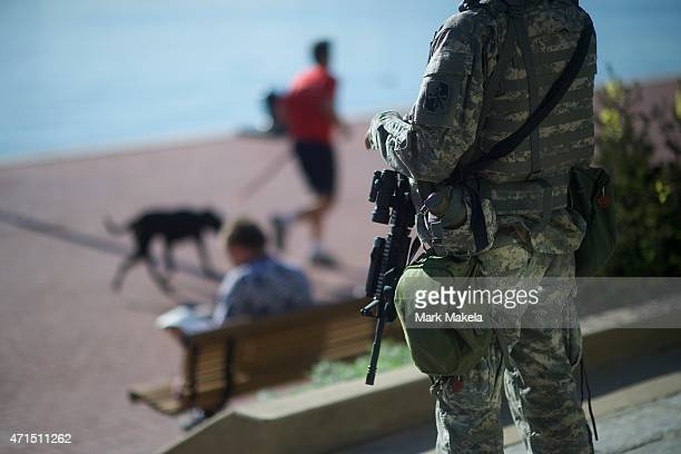 A member of the the National Guard monitors activity in the Inner Harbor while a man reads a newspaper and another runs with his dog following...