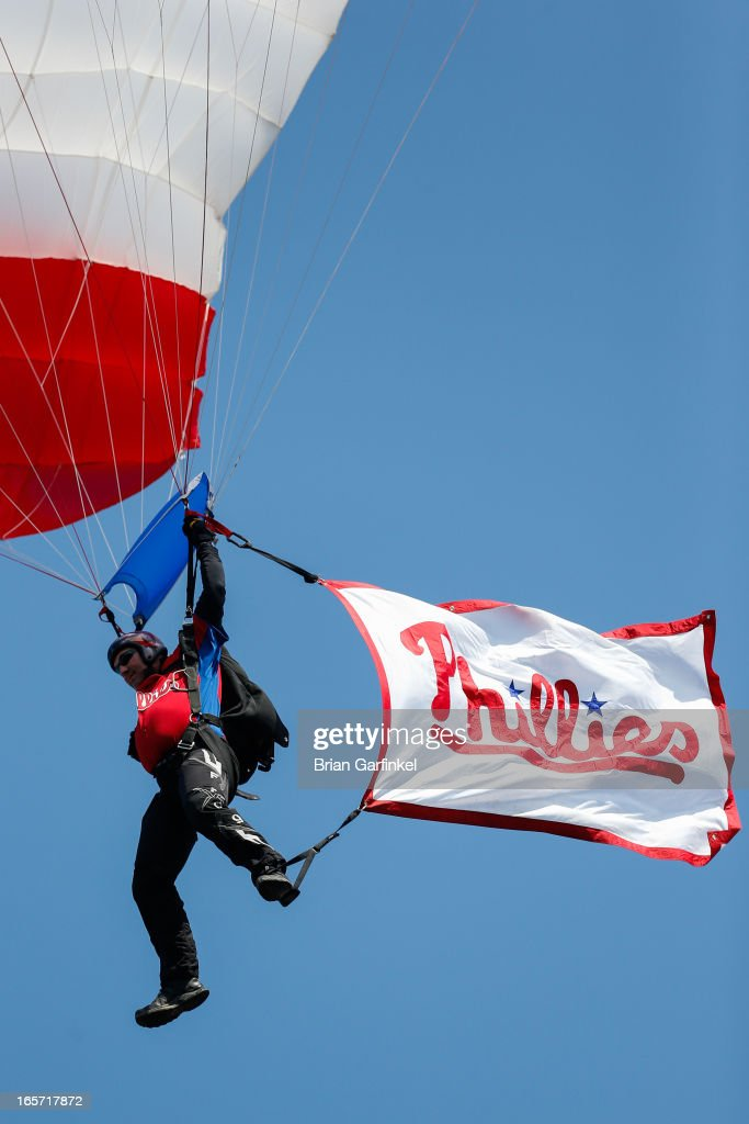 A member of the The United States Navy Parachute Team 'The Leap Frogs' parachutes into the stadium with a Philadelphia Phillies flag before the Opening Day game against the Kansas City Royals at Citizens Bank Park on April 5, 2013 in Philadelphia, Pennsylvania.