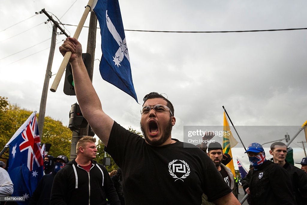 A member of the True Blue Crew baits the left leaning Anti Racism supporters from behind police lines at on May 28, 2016 in Melbourne, Australia. Violence erupted when participants in a 'Say No To Racism' rally protesting the forced closure of Aboriginal communities, off-shore detention centres and Islamophobia met with a counter 'Anti-Islam rally organised by the True Blue Crew and backed by the United Patriots Front.