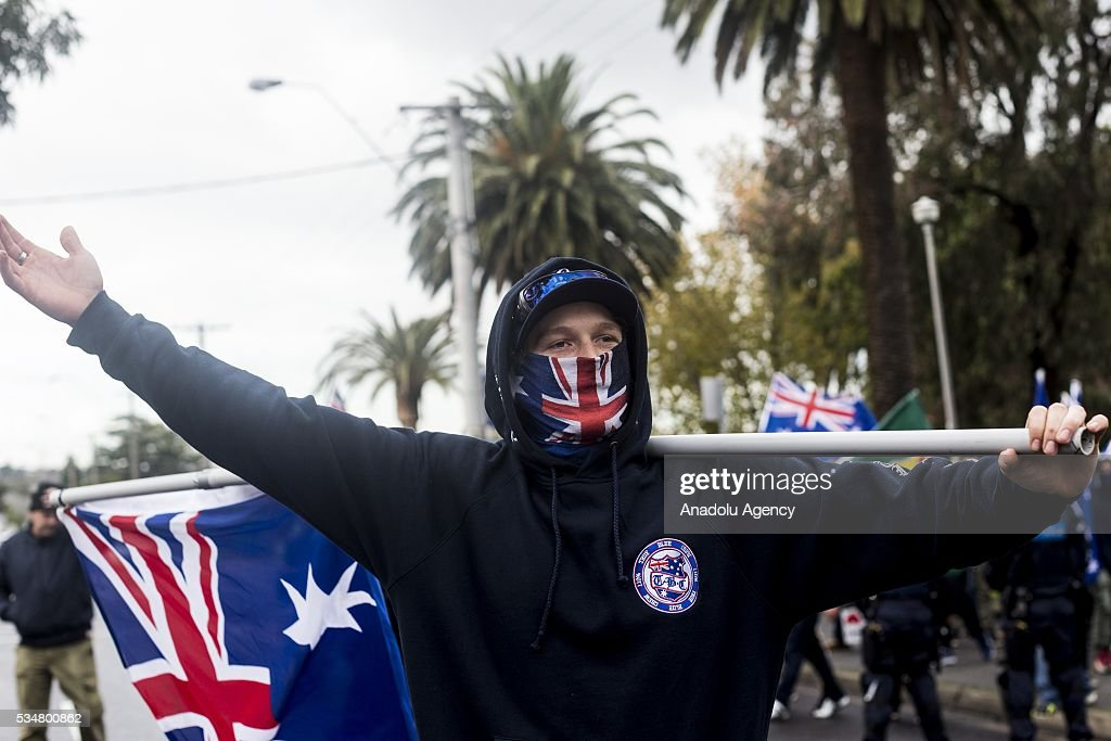 A member of the 'True Blue Crew' with an australian flag covering his mouth antagonises Anti-Fascists during a 'Say No To Racism' protest and a counter 'Stop the Far Left' rally in Coburg Melbourne, Australia on May 28, 2016. Seven men were arrested after a violent brawl erupted between rival protesters at an anti-racism rally in Melbourne's inner-north. Anti-Facists clashed with Anti-Islam nationalists who go by the name 'True Blue Crew'.