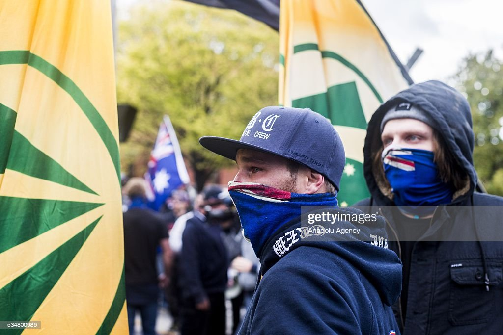 A member of the True Blue Crew with an Australian flag used as a mask walks past a UPF flag during a 'Say No To Racism' protest and a counter 'Stop the Far Left' rally in Coburg Melbourne, Australia on May 28, 2016. Seven men were arrested after a violent brawl erupted between rival protesters at an anti-racism rally in Melbourne's inner-north. Anti-Facists clashed with Anti-Islam nationalists who go by the name 'True Blue Crew'.