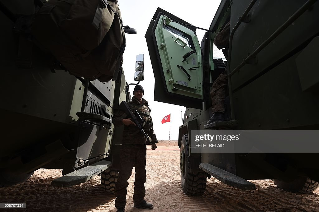 A member of the Tunisian army special forces takes part in a military exercise along the Libyan border on February 6, 2016, near the Ras Jedir crossing point. The construction of a barrier, which includes berms and trenches, along the Libyan border from Ras Jedir on the Mediterranean coast to Dhiba was announced in 2015 after a terrorist attack on the national museum in Tunis killed 22 people. / AFP / FETHI BELAID