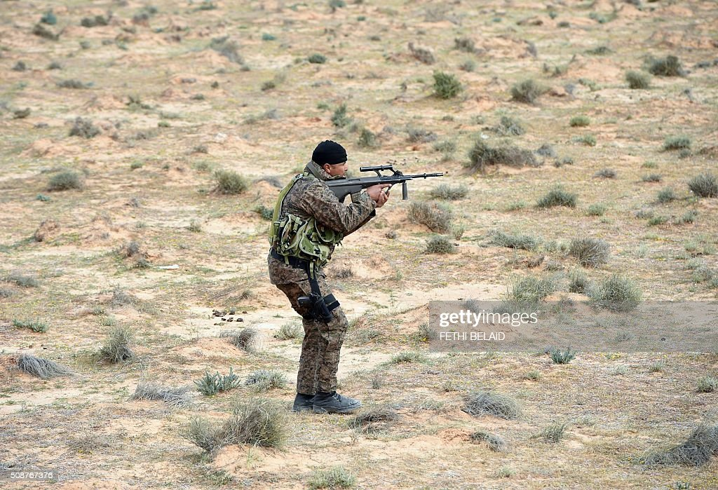 A member of the Tunisian army special forces takes part in a military exercise near a trench dug along the Libyan border on February 6, 2016, near the Ras Jedir crossing point. The construction of a barrier, which includes berms and trenches, along the Libyan border from Ras Jedir on the Mediterranean coast to Dhiba was announced in 2015 after a terrorist attack on the national museum in Tunis killed 22 people. / AFP / FETHI BELAID