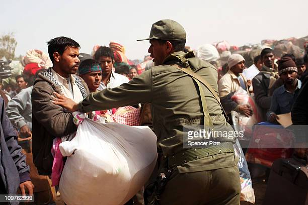 A member of the Tunisian military tries to hold back thousands of Bangladeshi migrant workers who recently crossed into Tunisia from Libya at a...