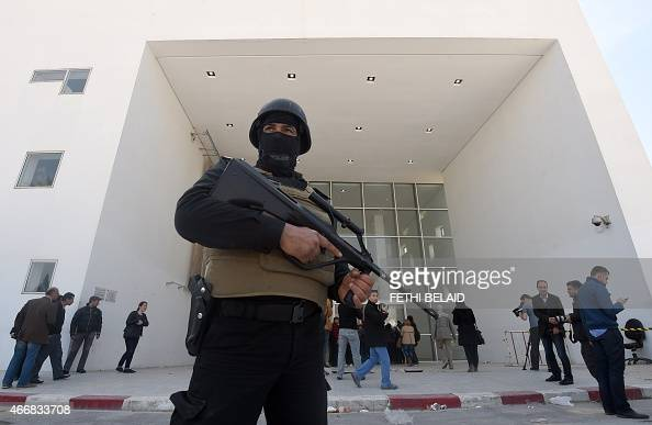 A member of the Tunisian security forces stands guard as journalists gather at the visitors entrance of the National Bardo Museum in Tunis on March...