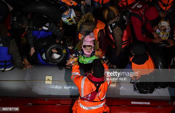 TOPSHOT A member of the Turkish Coast Guard holds a child as Syrian migrants wait aboard an inflatable dinghy after being rescued while attempting to...