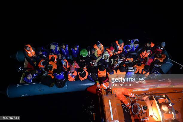 A member of the Turkish Coast Guard pulls an inflatable dinghy transporting Syrian migrants attempting to reach the Greek island of Chios in the...