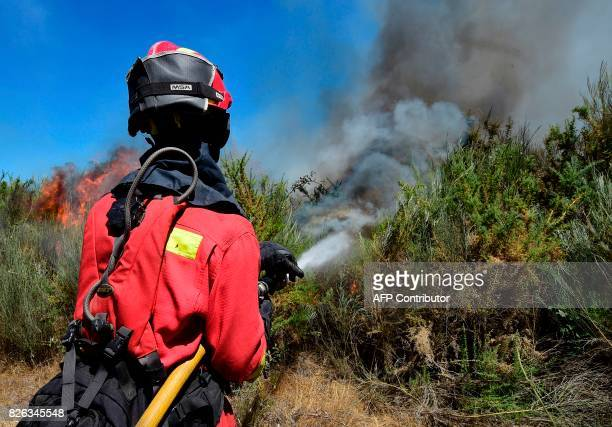 A member of the UME fights a wildfire in Vilardevos northwestern Spain on August 4 2017 / AFP PHOTO / MIGUEL RIOPA