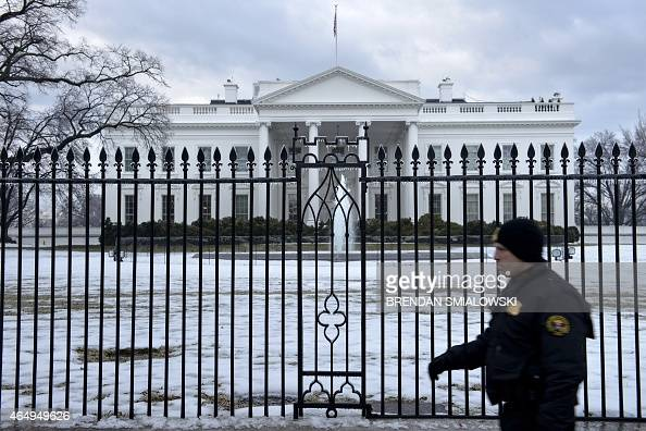 A member of the Uniformed Division of the Secret Service walks past an ice covered fence in front of the White House March 2 2015 in Washington DC...
