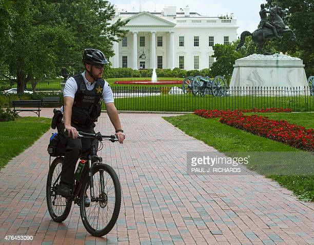A member of the uniformed US Secret Service on a partol bicycle rides through Lafayette Park across the street from the White House in Washington DC...