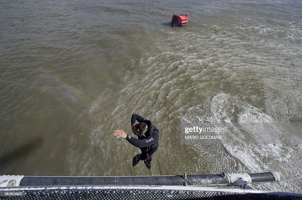 A member of the Uruguayan Air Force Operations, Training and Rescue Unit jumps from a helicopter during a drill at a beach of Salinas, near Montevideo, Uruguay on February 27, 2013. AFP PHOTO/Mario Goldman