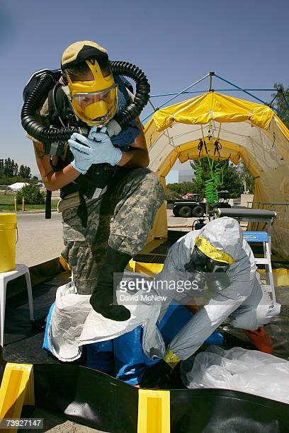 A member of the US Army Civil Support Team is decontaminated and helped out of his protective suit during an exercise simulating mass casualties from...