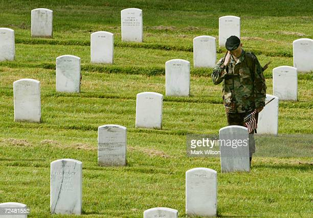A member of the US Army Infantry Regiment salutes after placing a flag on a grave stone at Arlington National Cemetary May 27 2004 in Arlington...