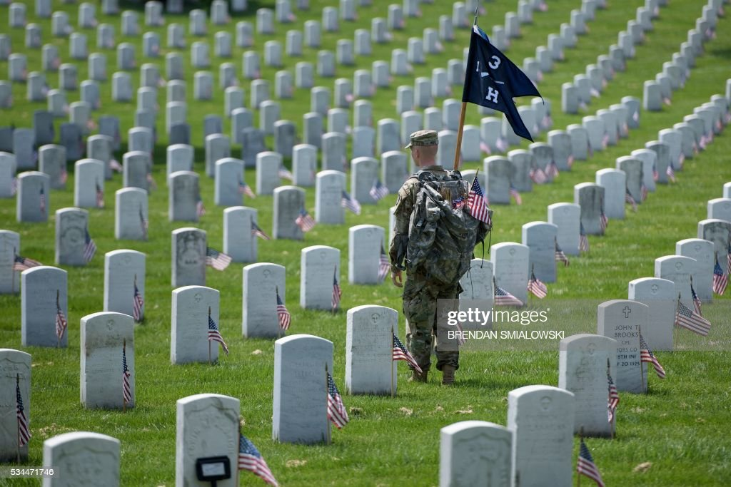 A member of the US Army looks on after placing American flags at graves at Arlington National Cemetery May 26, 2016 in Arlington, Virginia in preparation for Memorial Day. / AFP / Brendan Smialowski