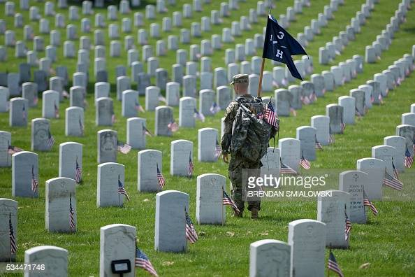 A member of the US Army looks on after placing American flags at graves at Arlington National Cemetery May 26 2016 in Arlington Virginia in...