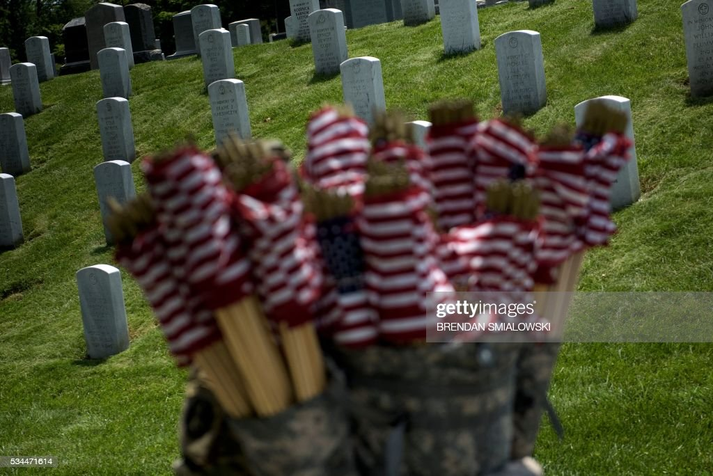 A member of the US Army waits to place American flags at graves at Arlington National Cemetery May 26, 2016 in Arlington, Virginia in preparation for Memorial Day. / AFP / Brendan Smialowski