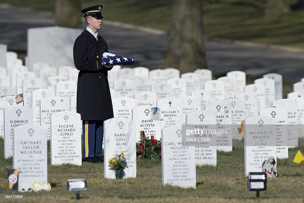 A member of the US Army's 3rd Infantry Regiment 'The Old Guard' holds a folded American flag during a burial service for US Army Captain Andrew Pedersen-Keel in Section 60 at Arlington National Cemetery in Arlington, Virginia, March 27, 2013. Pedersen-Keel, 28, was killed March 11 during an attack on a police station in Afghanistan. AFP PHOTO / Saul LOEB