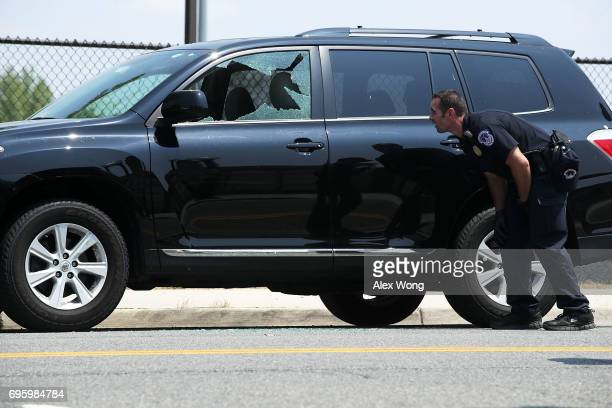 A member of the US Capitol Police observes a broken window on a vehicle at the scene of this morning's shooting at Eugene Simpson Stadium Park June...