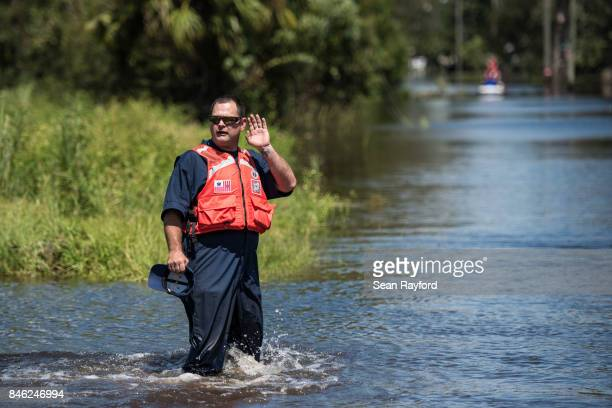 A member of the US Coast Guard gestures to a colleague during rescue operations in flood waters caused by Hurricane Irma September 12 2017 in...
