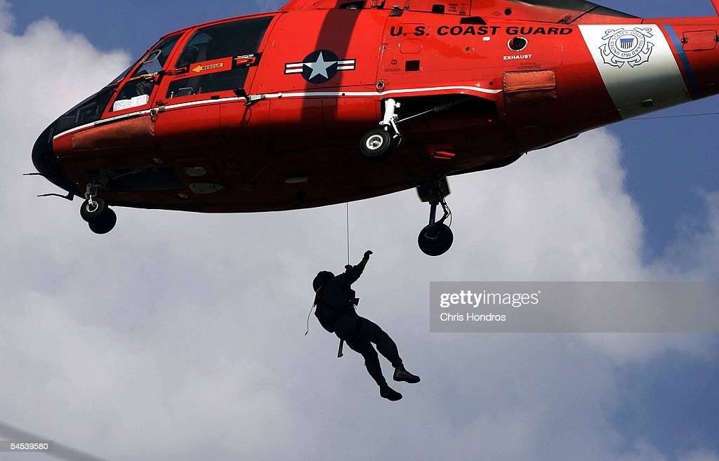 A member of the US Coast Guard glides back up to a helicopter via a dropped wire September 4 2005 in New Orleans Louisiana Coast Guard personnel are...