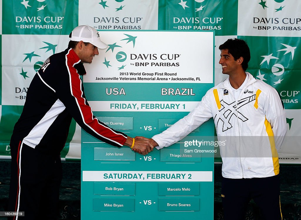 Member of the U.S. Davis Cup Team John Isner (L) shakes hands with Thomaz Bellucci of the Brazil Davis Cup Team following during the Davis Cup Draw ceremony first round between the U.S. and Brazil at the Times-Union Center on January 31, 2013 in Jacksonville, Florida.