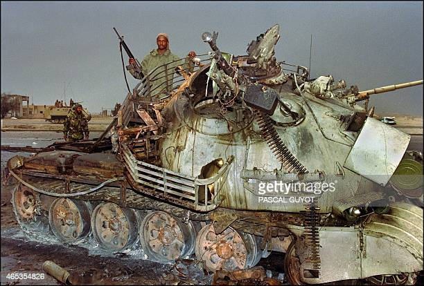 A member of the US Marine special forces inspects a destroyed Iraqi Army Russianmade T62 tank 27 February 1991 in a downtown of Kuwait City after the...