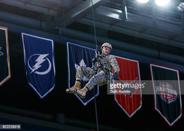 A member of the US Military repels from the catwalks of the Amalie Arena between periods for Military Appreciation Night between the Tampa Bay...